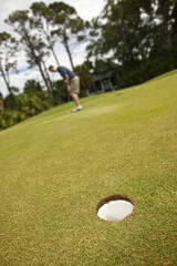 long putt on a putting green, focus on hole