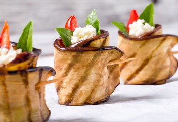delicious Eggplant Rolls with feta cheese, tomato and basil leaves, close-up