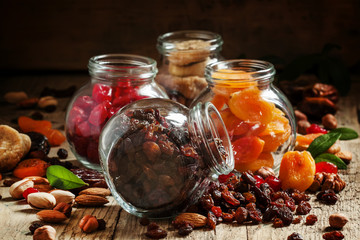 Dry dark raisins in a glass jar, assorted dried fruit on old woo
