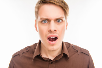 Close up photo of shocked angry young man with opened mouth