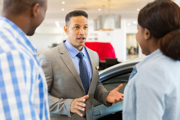 middle aged car salesman talking to african couple