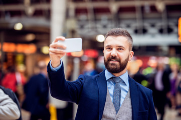 Hipster businessman with smartphone taking selfie, crowded train