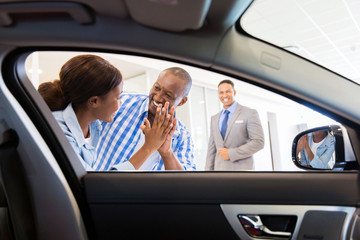 african couple at the dealership buying new car