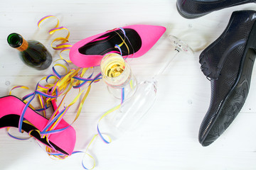 ladies pink high heela and black mens shoes lying between champa