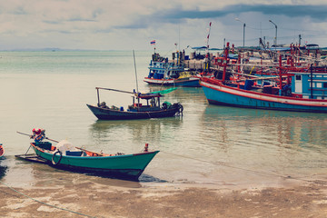 Old Harbour with fishing boats, ship and docks in Thailand.