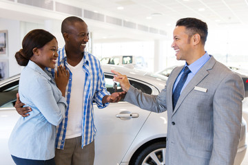 mid age car salesman handing over new car key to couple