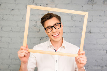 Cheerful happy man in glasses holding wooden frame
