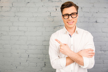 Attractive  young smiling man in white shirt pointing away