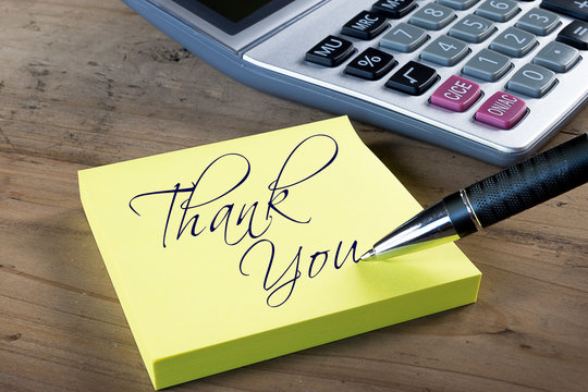 "Yellow sticky note with ""Thank you"" written with pen.