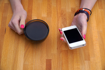 girl sitting in cafe the table and drinking black coffee, using your smartphone