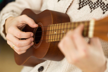 Woman's hand playing ukulele.