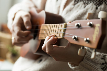 Woman's hand playing ukulele.
