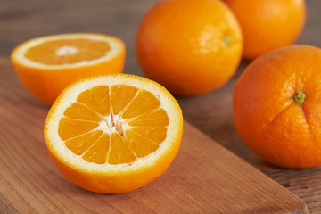 Orange. Cut orange on a wooden cutting board.
