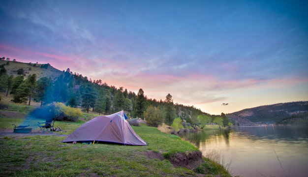 camping site on scenic mountain lake at sunset