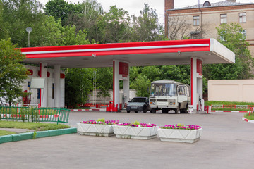 bus and car refuel at gas station