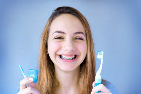 Beautiful smiling girl with retainer for teeth brushing teeth .