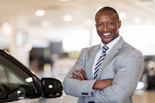 african american car dealership principal standing