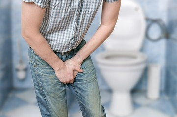 Man with prostate problem in front of toilet bowl. Incontinence concept.
