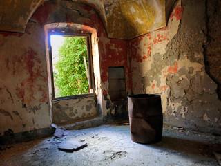 Rusty steel drum inside abandoned room - landscape color photo