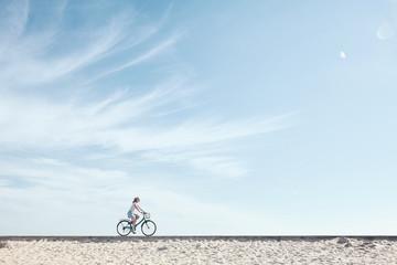 Girl enjoying bike ride under sky