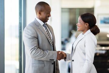 african car dealer handshake with customer