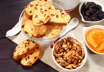 Homemade biscotti are laid out in the form of words next to a large cup of hot black coffee on vintage rustic table