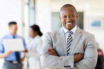 african salesman standing at car dealership