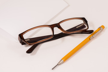 Glassses, pencil and notebook paper