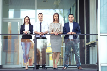 Group of four young business people on a coffee break in front of the office. They are leaning on the railing of the balcony and looking at camera.