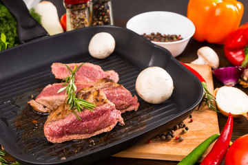 Rare Seasoned Beef Sizzling in Pan with Veggies