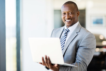 afro american vehicle sales consultant using laptop