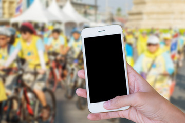 Hands woman are holding touch screen smart phone,tablet on blurred campaign many people  biking bicycle background.