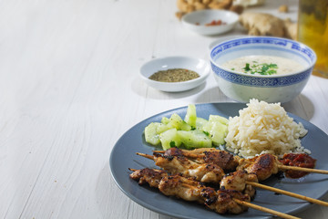 Asian satay meat skewers with rice, cucumber salad and peanut sa