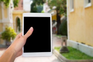 Hands woman are holding touch screen smart phone,tablet on blurred road and building with nature background.