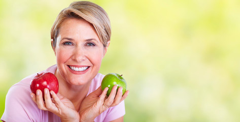 Wall Mural - Mature smiling woman with apple.