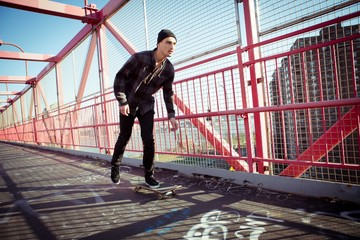 Skateboarder cruise on bridge