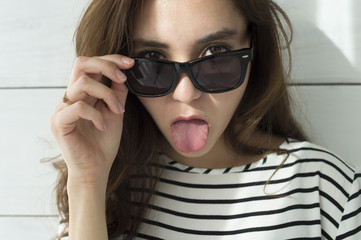 Young woman with sunglasses has issued a tongue