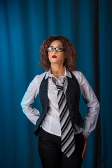 Attractive young brunette woman with curly hair in business clothes posing against blue curtain