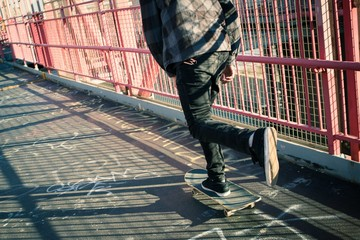 Long shadow of a skateboarder cruising through crosswalk. Photographed in Feb 2016.
