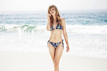 Wall Mural - Stunning woman in bikini at beach, portrait
