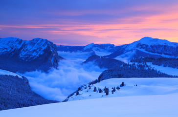 Fotomurales - Clouds in the valley of a mountain range in French Alps during a colorful sunset.