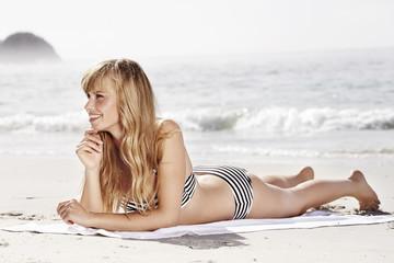 Wall Mural - Bikini babe sunbathing on beach towel