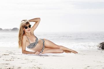 Wall Mural - Beach babe sunbathing in bikini and shades