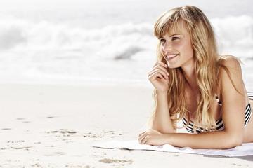 Wall Mural - Beautiful woman sunbathing on beach, smiling