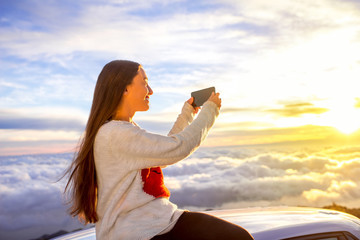Young woman in sweater with heart shape photographing with smart phone beautiful cloudscape sitting on the car roof above the clouds on the sunrise