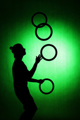 silhouette of a juggler with rings on a green background