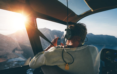 Female tourist on helicopter tour taking pictures Wall mural