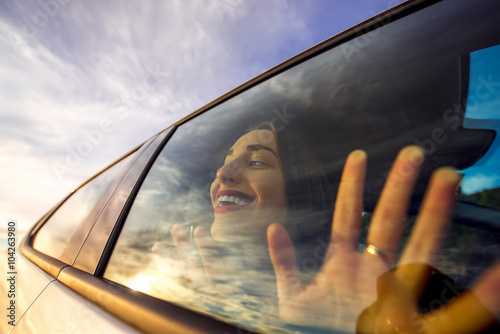 Funny and pretty woman looking through the window with sky