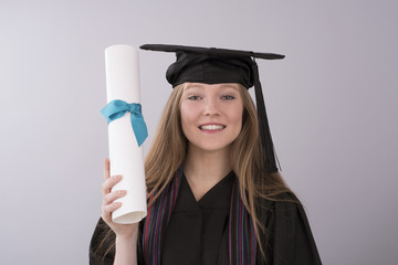 Young graduate in cap and gown with diploma