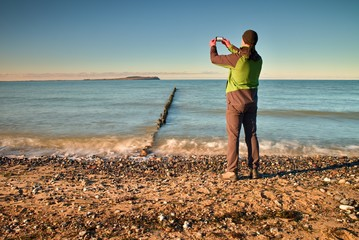 Tourist hold cellphone, take picture of autumn  sea scenery at breakwater.  Vivid and vignetting effect.